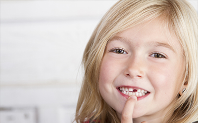 A young girl pointing to her mouth where a tooth is missing