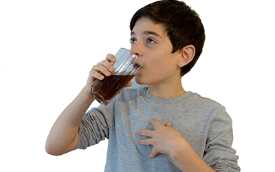 child drinking a glass of soda