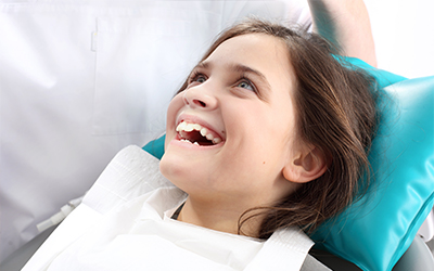 A young girl sitting in a dental chair