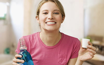 Woman with mouthwash