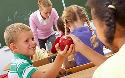 Children in classroom ahnding apple over to another child