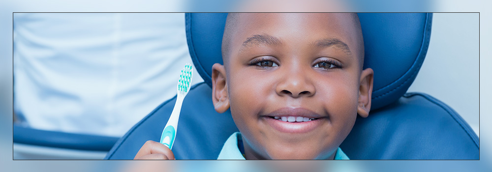 Young boy in dental chair holding toothbrush