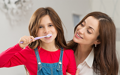 A parent helping their young child brush their teeth