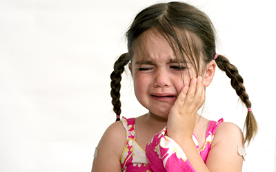 A young girl holding the side of her mouth in pain