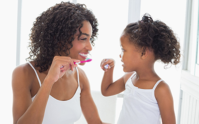 A mother and young girl brushing their teeth together
