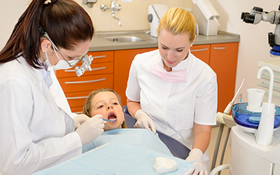 A dentist looking at a young girl's teeth